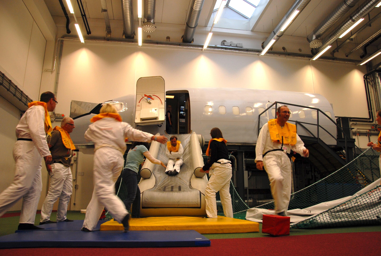 Passagiere rutschen die Notrutsche herunter und laufen vom Simulator weg zur Seite
