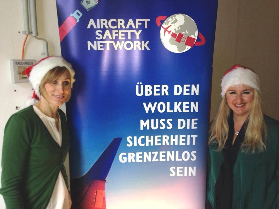 Das Bild zeigt Barbara Pencik und Barbara Letuha mit Weihnachtsmütze vor dem Werbebanner von ASN.
