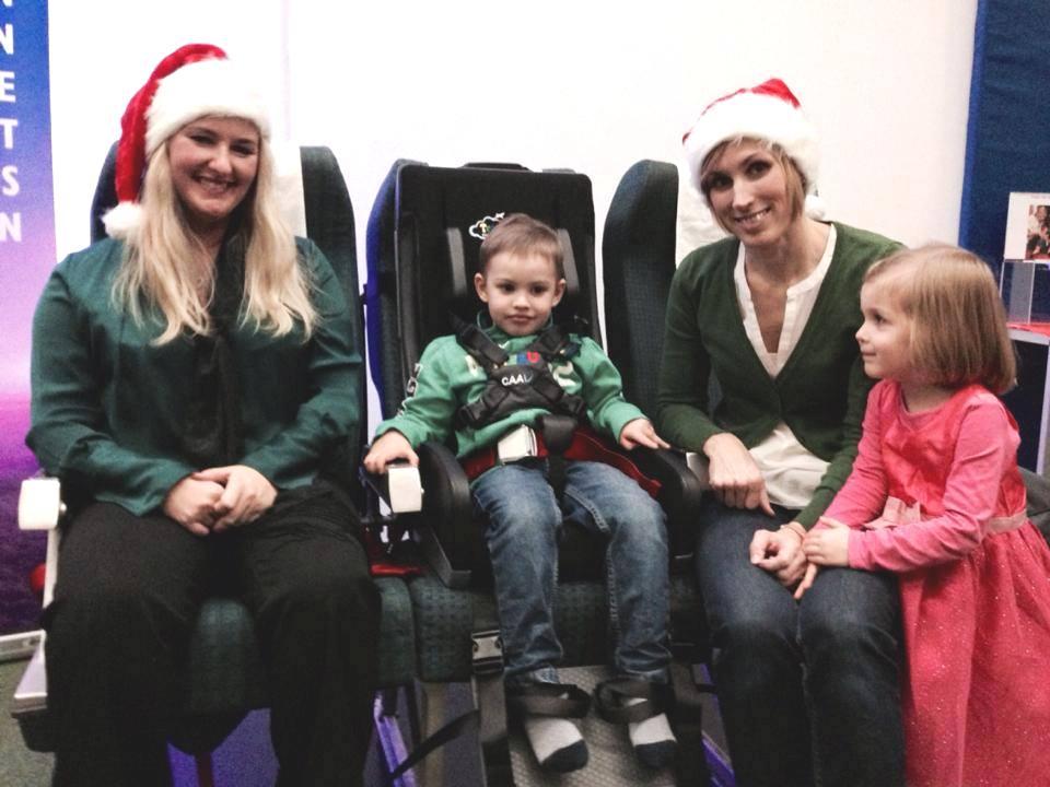 Das Bild zeigt das ASN Team, daneben ein Kind, das den Travel Chair testet